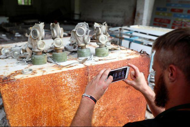 Un touriste prend une photo dans les ruines de la centrale nucléaire de Tchernobyl.