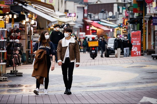 Deux passants masqués dans une rue de Séoul.