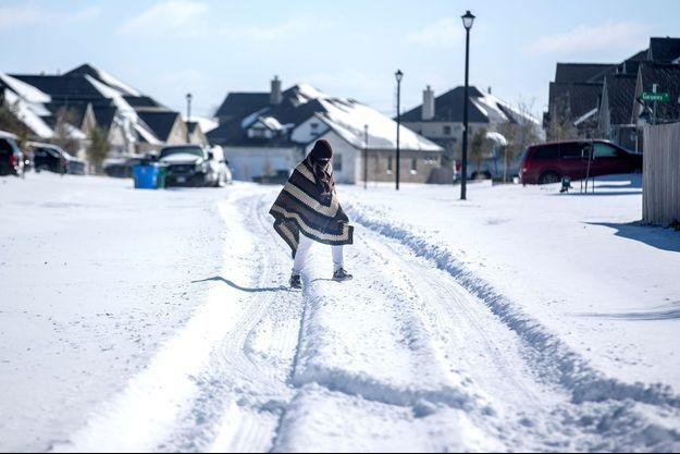 Un homme se rend chez son ami dans un quartier sans électricité alors que la neige recouvre le quartier de BlackHawk à Pflugerville, Texas.
