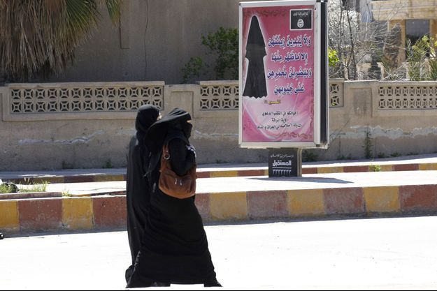 Des femmes voilées passent devant un panneau d'affichage qui comporte un verset du Coran exhortant les femmes à porter le voile intégral, dans la province de Raqqa.