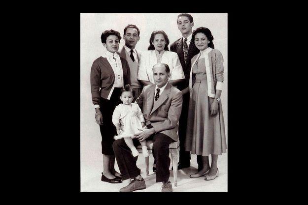 Avril 1954 : Mohammed V est en exil à Madagascar. Le roi a posé avec six de ses sept en enfants chez un photographe local. De gauche à droite : Aïcha, Hassan, futur roi Hassan II, Malika, Abdellah, et Nezha. Sur les genoux du patriarche, la plus jeune des princesses, Amina.