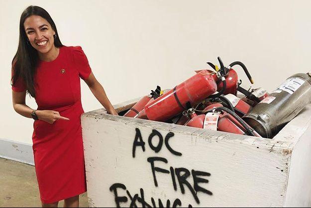"""Alexandria Ocasio-Cortez éclate de rire devant cette caisse d'extincteurs où l'on lit """"AOC"""", son surnom."""