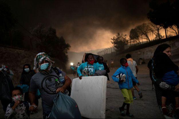 Les réfugiés et les migrants transportant leurs affaires fuient un incendie qui brûle au camp de Moria sur l'île de Lesbos, Grèce.