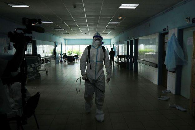 Un agent de santé, portant une combinaison de protection et un masque facial, marche alors qu'il se prépare à désinfecter un couloir d'un hôpital après qu'un cas d'Ebola a été confirmé à Abidjan.