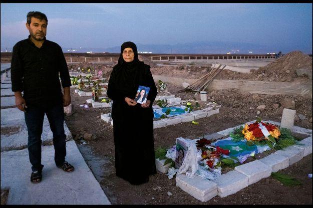 Cimetière de Derik, Rojava. Sadia Khalaf, accompagnée de son fils Adil, devant la tombe de sa fille Hevrin, tuée avec son chauffeur le 12 octobre.