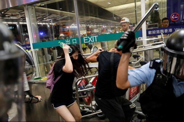 Les manifestants ont été délogés de l'aéroport de Hong Kong par la police anti-émeute.