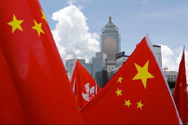 Un bâtiment hongkongais au-dessus de drapeaux chinois.