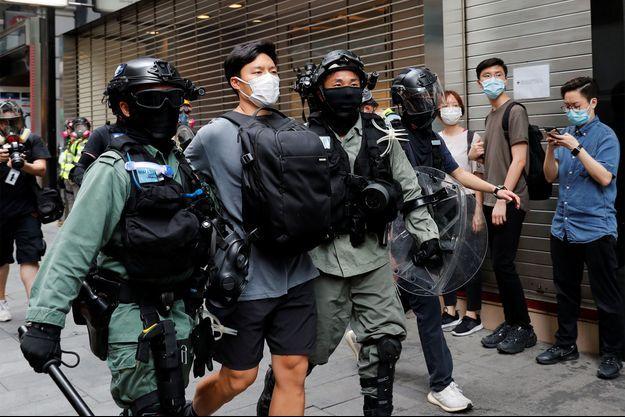 Des policiers anti-émeute arrêtent un manifestant qui proteste contre la deuxième lecture d'une loi controversée sur l'hymne national.