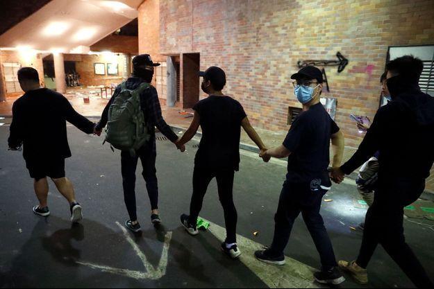 Des jeunes étudiants de l'Université polytechnique de Hong Kong se rendent aux autorités.