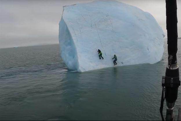 Mike Horn et l'un de ses acolytes grimpent sur un iceberg avant qu'il ne se renverse dans l'eau.
