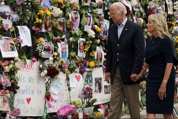 Joe et Jill Biden devant un mur du souvenir improvisé sur un grillage métallique, couvert de photos de victimes et de disparus.