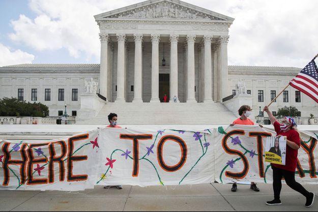 """Manifestation de """"dreamers"""" devant la Cour suprême à Washington, le 18 juin dernier, après une décision de l'instance donnant tort à l'administration Trump. Sur la banderole : """"Ici pour rester""""."""