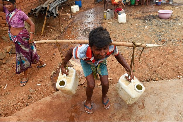 Un homme transporte des bidons d'eau, en Inde.