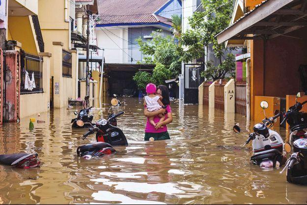 Une femme tient son enfant dans les bras, dans les inondations en Indonésie.