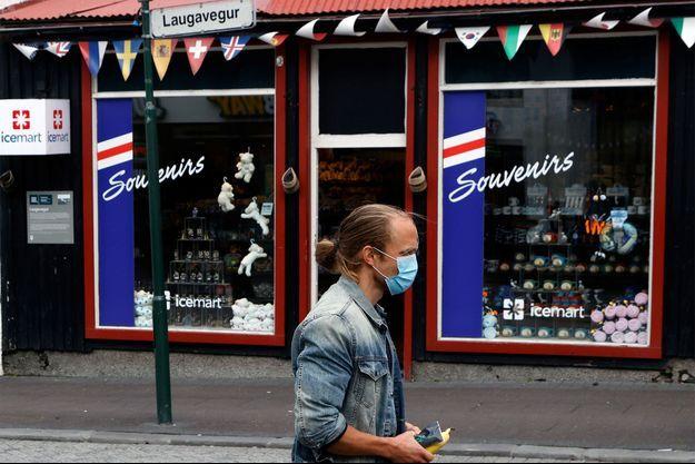 Un homme marche devant une boutique de souvenir de Reykjavík.