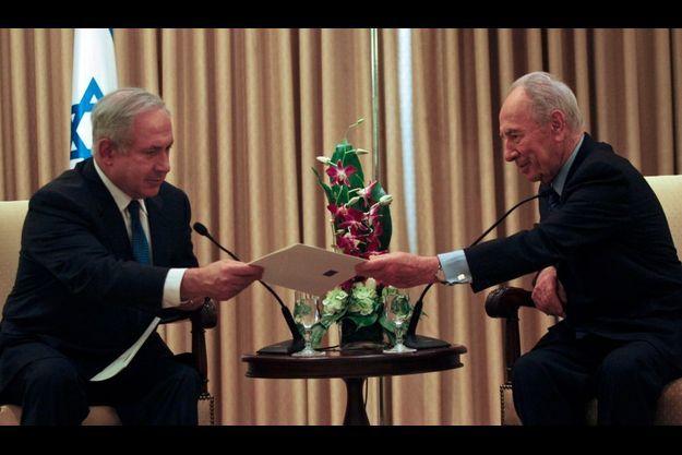 Comme le veut la coutume, Shimon Peres (à dr.) a remis la lettre de nomination à Benyamin Netanyahou.