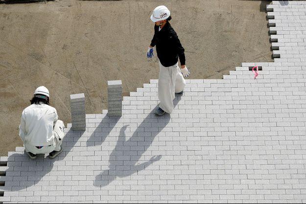 Des ouvriers sur un des chantiers des JO, à Tokyo.