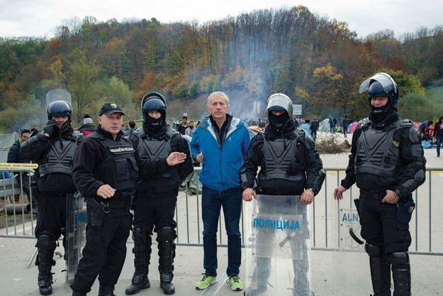 A Velika Kladusa, en Bosnie-Herzégovine : la police bosniaque à la frontière de l'Union européenne. Derrière, le 26 octobre 2018, des migrants qui espèrent entrer dans l'espace Schengen. Un million d'entre eux avaient emprunté la route des Balkans en 2015. Seulement 16 000 cette année. Mais la crise migratoire s'est muée en crise politique