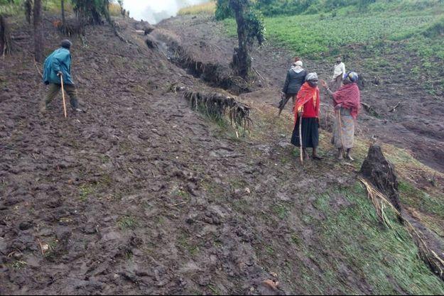 Des gens marchent dans la boue après les fortes pluies qui ont provoqué des glissements de terrain dans le village de Parua, au Kenya.