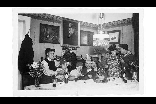 Sous le portrait du Führer. Soldats et sous-officier fêtent une permission. Dans la salle à manger, le cadre du dictateur fait pendant à celui des vieux parents.