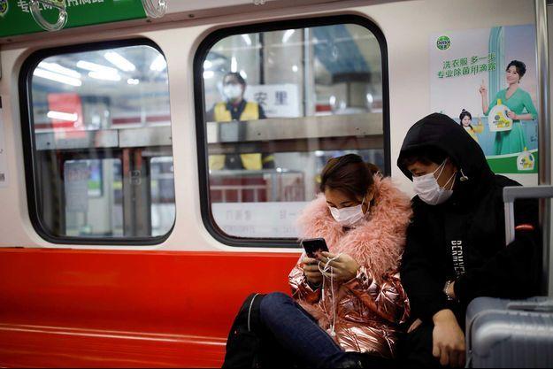 Des voyageurs dans le métro, à Pékin.