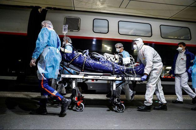 Gare d'Austerlitz, le 1er avril, à Paris : un patient est conduit à bord d'un TGV sanitaire, direction la Bretagne.