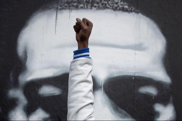 Un habitant de Minneapolis lève le poing devant un portrait de George Floyd.