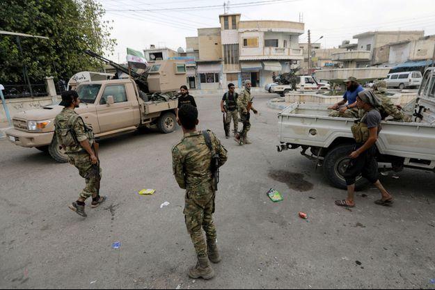 Des combattants rebelles syriens soutenus par la Turquie marchent près d'un camion muni d'une arme dans la ville frontalière de Tal Abyad, en Syrie.