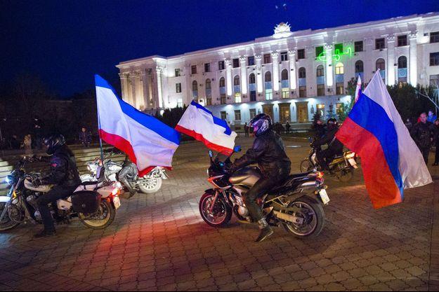 Sur la place Lénine de Simferopol, la capitale de la Crimée, des motards brandissent le drapeau russe, dimanche.