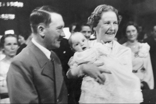 Edda Göring dans les bras de sa mère avec son parrain Adolf Hitler, en novembre 1938 lors de son baptême.