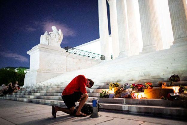 Un homme s'agenouille devant la Cour suprême, à Washington, vendredi soir.