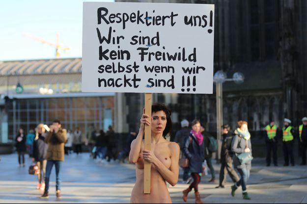 """L'artiste contemporaine Milo Moire a défilé nue dans les rues de Cologne avec cette pancarte: """"Respectez nous, nous ne sommes pas du gibier même quand nous sommes nues""""."""
