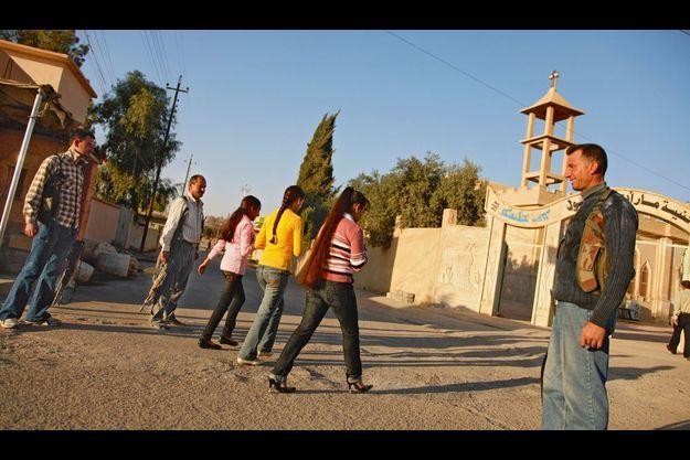 Irak. A Karmless, trois jeunes filles se rendent à l'office de 16 heures sous haute surveillance. Les adolescents fréquentent assidûment l'église.