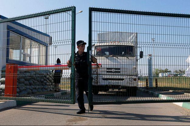 Un garde-frontière russe ouvre la porte pour laisser passer le camion humanitaire, dans la région frontalière de Rostov.