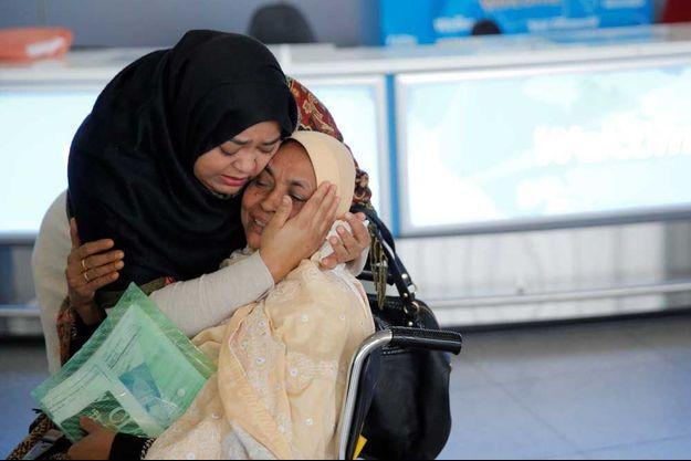 Une mère réconforte sa fille à l'aéroport JFK de New York samedi soir.