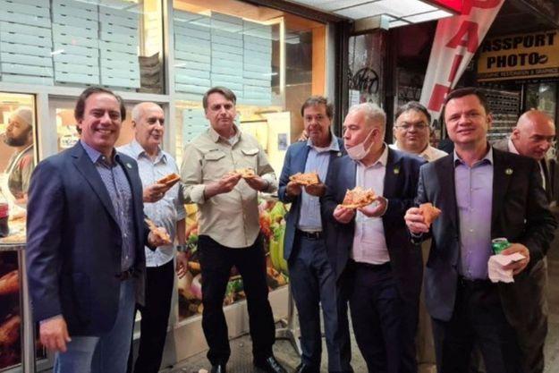 Le président brésilien Jair Bolsonaro (3d L) mange une pizza avec le président de la Caixa Economica Federal Bank Pedro Guimaraes, le général Luiz Eduardo Ramos, le ministre du Tourisme Gilson Machado Neto, le ministre de la Santé Marcelo Queiroga et d'autres politiciens dans une rue avant l'Assemblée générale des Nations Unies à New York.