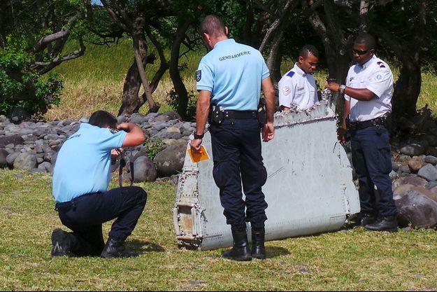 Des gendarmes inspectent le bout d'aîle retrouvé à La Réunion.