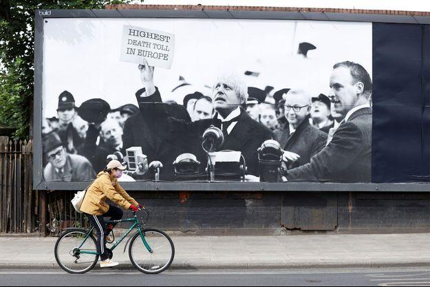 """Un personne portant un masque passe en vélo devant une affiche montrant le Premier ministre britannique brandissant un feuille sur laquelle il est écrit: """"Plus forte mortalité d'Europe""""."""