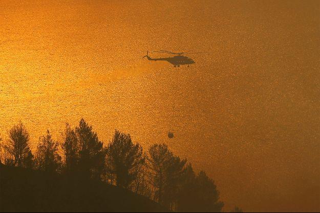 Un hélicoptère des pompiers survole un incendie en Grèce.