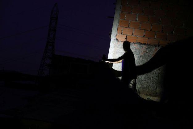 Un homme s'éclaire avec une lampe de poche au Venezuela, paralysé par une nouvelle panne d'électricité.