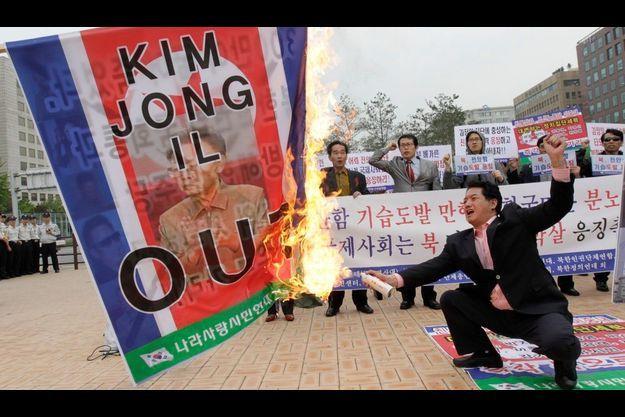Un manifestant sud-coréen brûle un drapeau à l'effigie du dirigeant de la Corée du Nord.