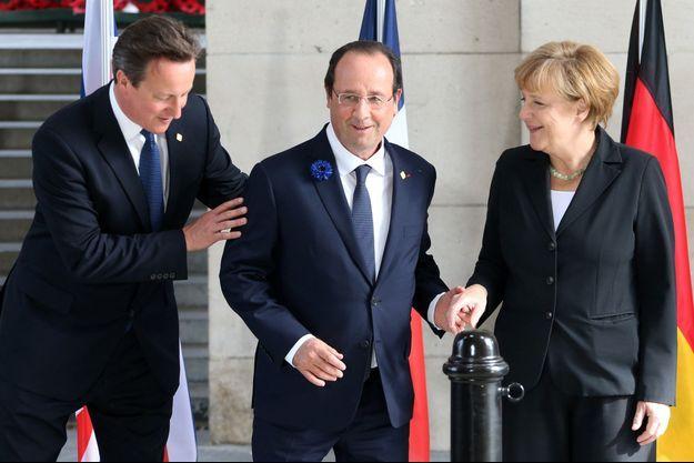 Le président de la République François Hollande, entre le Premier ministre britannique David Cameron et la chancelière allemande Angela Merkel, le 26 juin 2014.