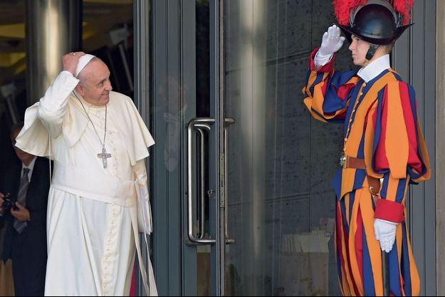 A la sortie de la salle Paul-VI, le Pape rejoint, à pied et sans solennité, ses appartements de Santa Marta. Sur le chemin, il salue un Garde suisse.