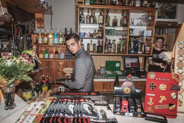 Sanny, 17 ans, allemand, fan de Hitler. Le 16 janvier au bar Golden Lion, le jeune homme travaille au milieu de symboles prisés des suprémacistes blancs : croix de fer, soleil noir (ersatz de la croix gammée) et revue officielle du parti néonazi NPD.