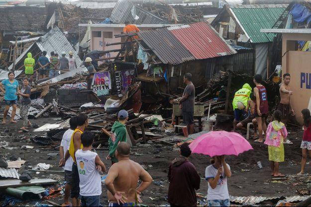 Des habitants debout près de leurs maisons ravagées.