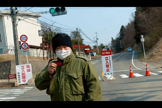 Vendredi 1er avril, à Miyakoji Hiroki, 28 ans, montre les pastilles d'iode qu'il doit avaler en cas d'accident grave. Sur son visage, un simple masque antipollution. A l'arrière-plan, deux policiers en tenue de protection blanche inspectent un véhicule.