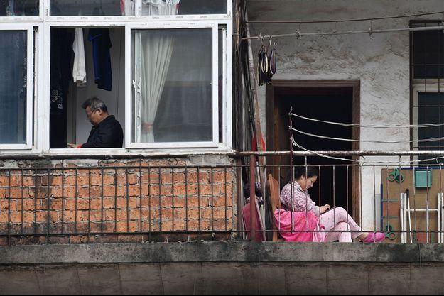 Une femme regarde son téléphone portable alors qu'elle est assise sur un balcon près d'un homme debout près d'une fenêtre dans un complexe résidentiel à Wuhan.
