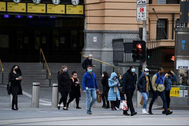 Des piétons à Melbourne, où les cas de coronavirus sont de plus en plus nombreux.