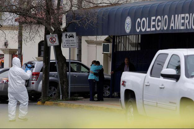 Une femme sert un élève dans ses bras devant le collège de Monterrey, au Mexique, où une fusillade a éclaté.