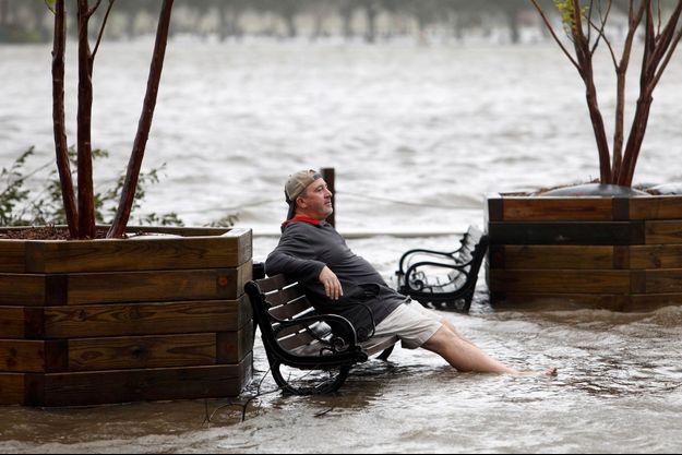 A Wilmington, un homme, résigné, se repose, les pieds dans l'eau alors que la Cape Fear River a inversé son cours...